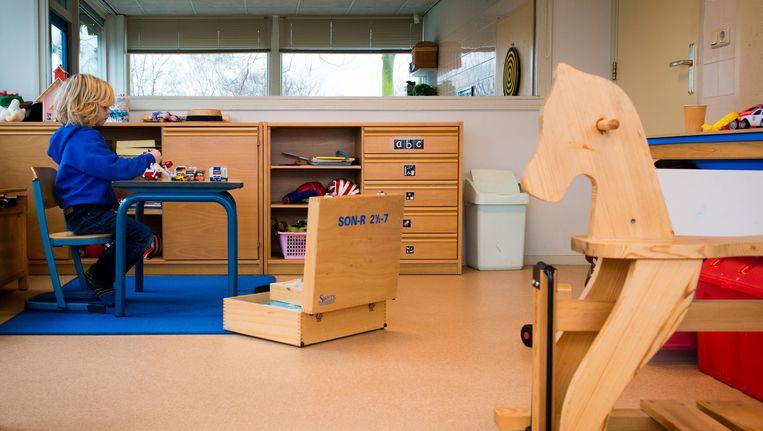 Een jongen speelt met auto's in een speelkamer van een jeugdhulpverleningscentrum. Beeld anp