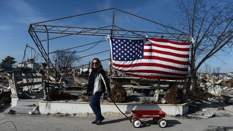 Een Amerikaanse vrouw rijdt met een wagentjes langs haar huis om te kijken of ze nog waardevolle spullen dan vinden tussen het puin Beeld epa
