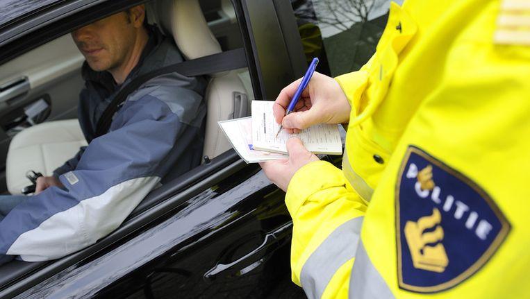 Agent schrijft bekeuring uit. © ANP Beeld