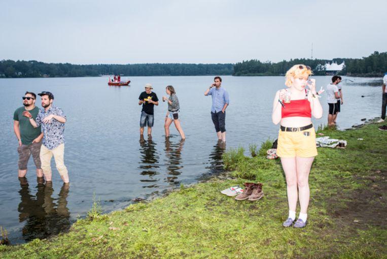 Mensen zoeken verkoeling in het water tijdens het optreden van Tyler, The Creator. Beeld Jan Mulders