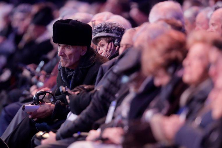 Overlevenden van de nazigruwel volgen de toespraken.