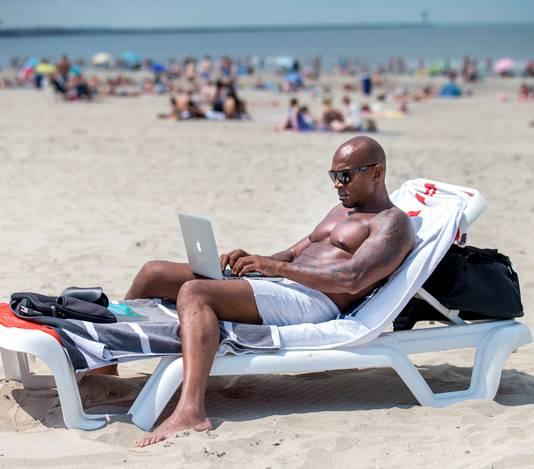 Een vakantieganger surft op zijn laptop. Foto: Jerry Lampen