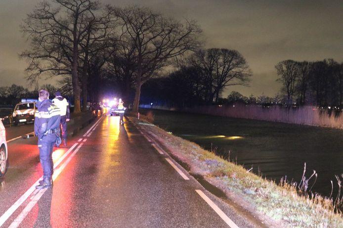 Auto te water in Lieren. De koplampen van de wagen zijn nog in het kanaal zichtbaar.