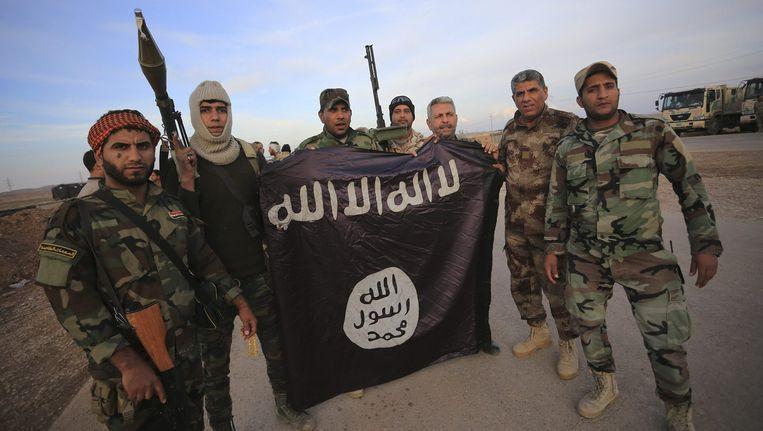 Sjiitische strijders poseren met een neergehaalde IS-vlag in Jalawla. (Archiefbeeld)