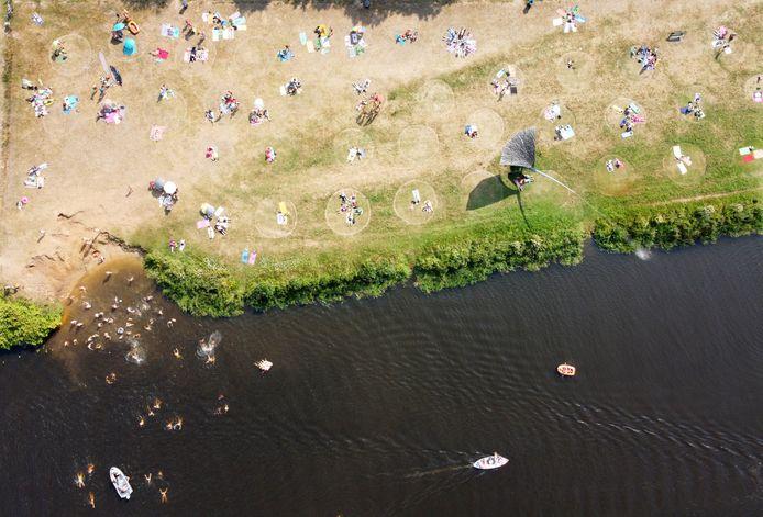 Gemaaide ringen in het gras aan de oevers bij de Vecht in Ommen moeten voorkomen dat de zonnende toeristen te dicht bij elkaar gaan liggen.