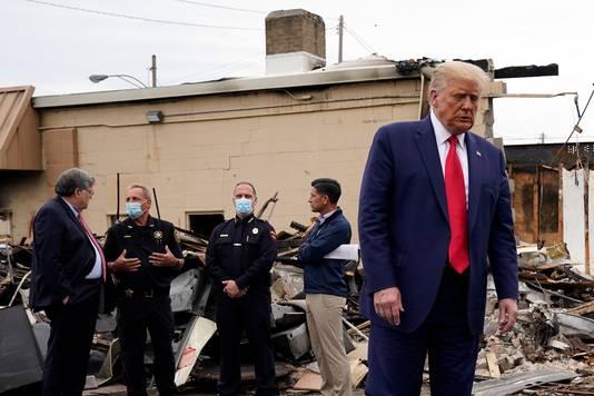 Donald Trump praat met agenten terwijl hij de schade opneemt in Kenosha.
