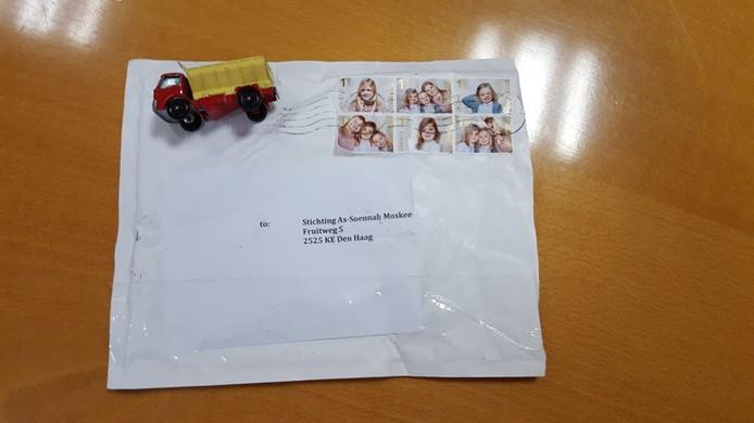 In de envelop zat ook een speelgoedvrachtwagentje.