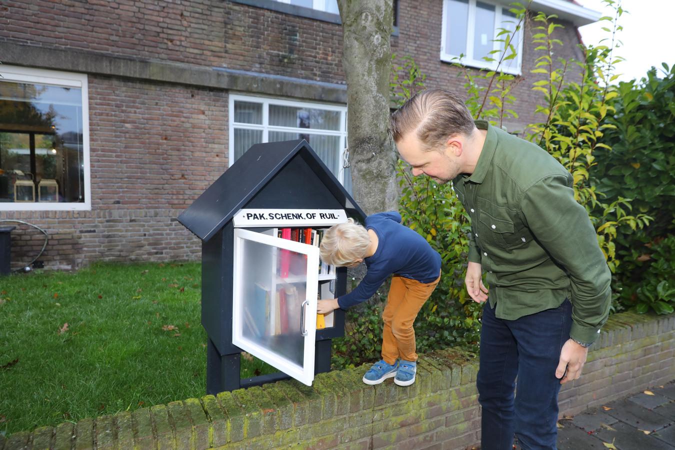 Ton Vogels samen met zoon Florian en zijn boekenkastje.