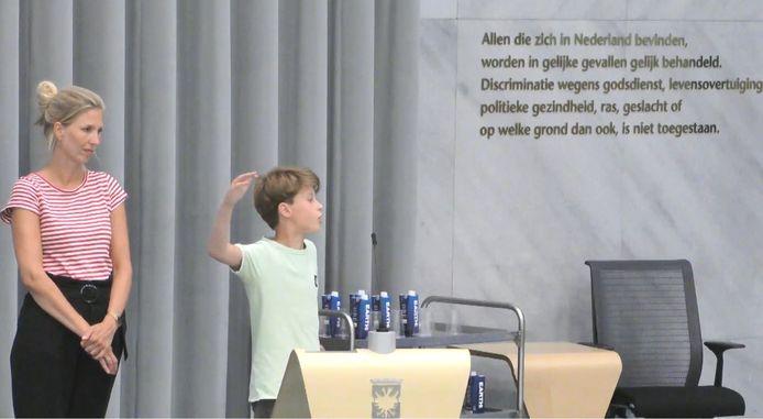 Teun van der Laan (r) legt de gemeenteraad van Arnhem uit wat psychomotorische therapie voor hem betekende. Links zijn moeder Joyce Roozeboom.