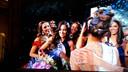Nicky (middenachter) kijkt toe hoe de nieuwe Miss Universe gefeliciteerd wordt.