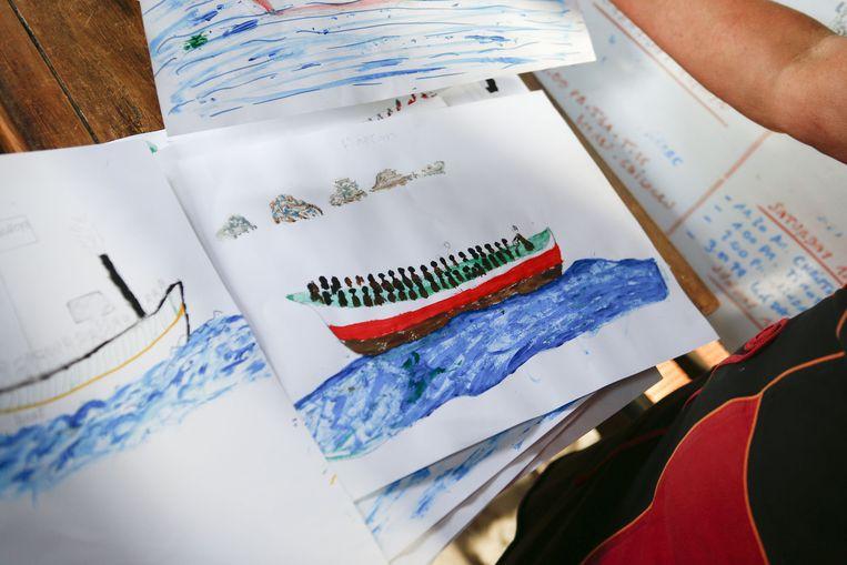 Chris uit Ukkel geeft les in het schooltje en toont de tekeningen die de kinderen maakten van hun overtocht van de Middellandse Zee.