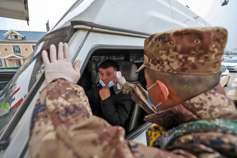 Een militair meet de lichaamstemperatuur van een automobilist bij een tolweg in Wuhan. Beeld EPA