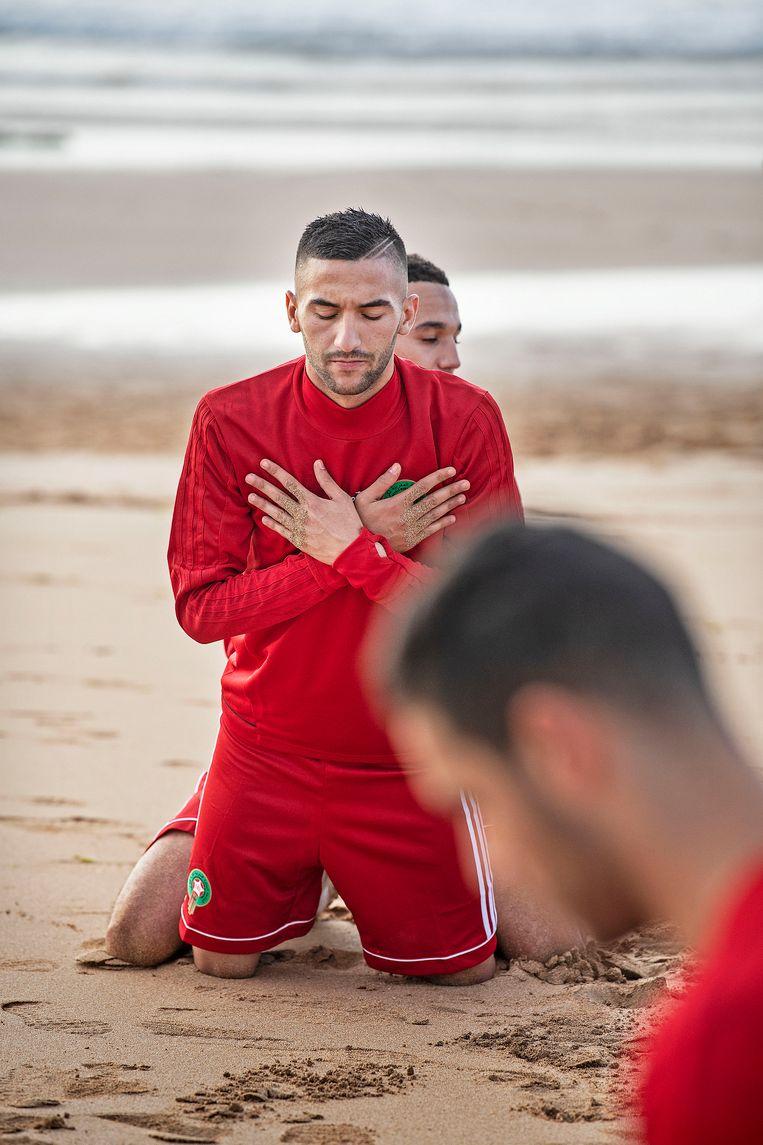 Hakim Ziyech doet rek- en strekoefeningen tijdens een eerste training op het strand. Beeld Guus Dubbelman/ de Volkskrant