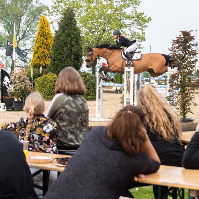Toeschouwers van Jumping Etten-Leur zien hoe Anoek van der Pluijm met haar paard een sprong maakt.