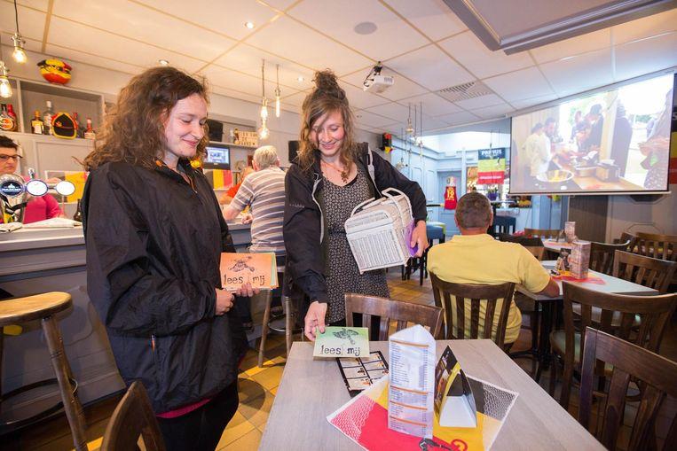 Eli Bijnens en haar zus Riene leggen hun brieven in een café om de aandacht te vestigen op de situatie van vluchtelingen in Griekse kampen.
