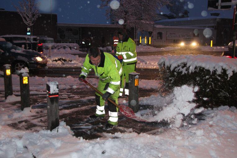 Stadsarbeiders ruimen sneeuw en strooien zout in schoolomgevingen.