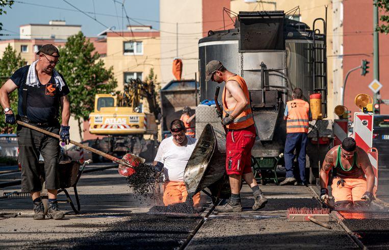 Duitse wegwerkers aan de slag in een bloedheet Berlijn. Beeld ALEXANDER BECHER/EPA