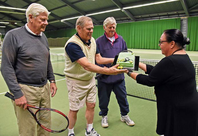 Tennisser Huub Nijsten ontvangt een taart van Ilse Walraven voor 40 jaar trouwe dienst in het Terneuzense Racketcentrum. Naast hem staan zijn broers Herman (links) en Jan (rechts).