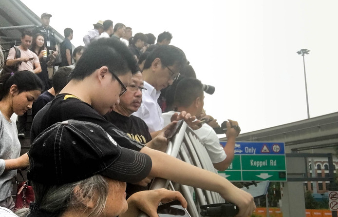 Publiek in Singapore wacht op de passage van Trump en Kim.