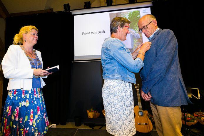Frans van Delft krijgt zijn onderscheiding opgespeld door zijn vrouw terwijl burgermeester Willemijn van Hees keurig anderhalve meter afstand houdt.