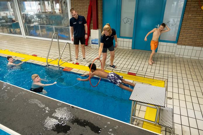 Jens, Jurian, Esey en Wesley duiken door de hoepels tijdens het schoolzwemmen in het Berghuizer Bad.