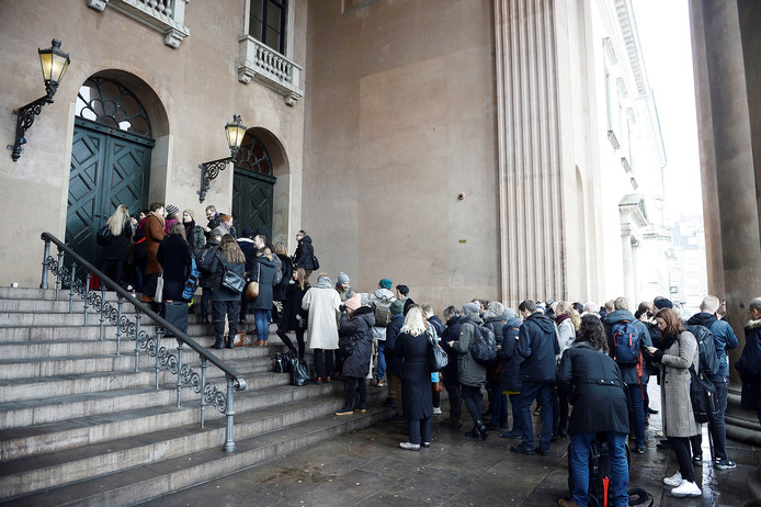 Pers en toehoorders staan in de rij voor het proces.
