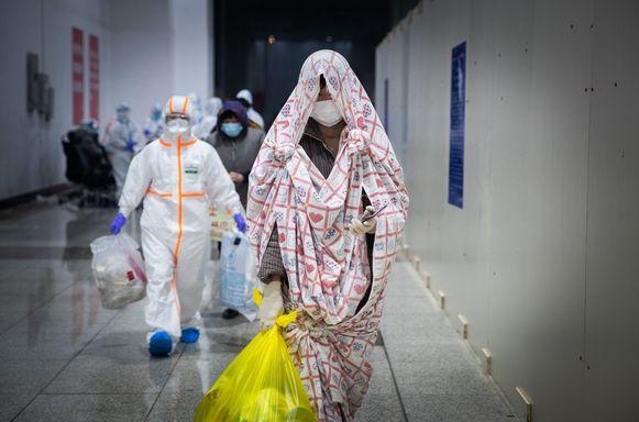 Medisch personeel begeleidt besmette personen naar hun kamer in het nieuwe Fangcang hospitaal in Wuhan.