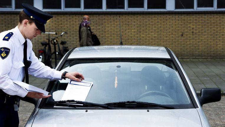 Een politieagent stopt zaterdag een vragenformulier achter een ruitenwisser van een auto bij winkelcentrum De Ridderhof in Alphen aan den Rijn in de hoop getuigen te vinden. Beeld anp