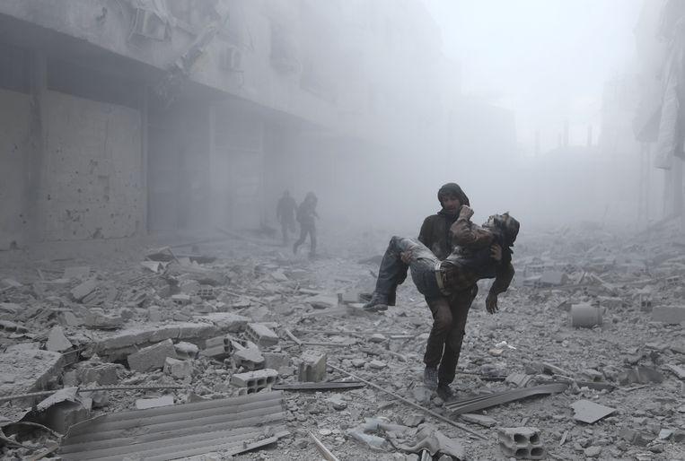 Een gewonde man wordt weggedragen na een aanval op het stadje Arbin bij Damascus. De foto werd gisteren genomen.