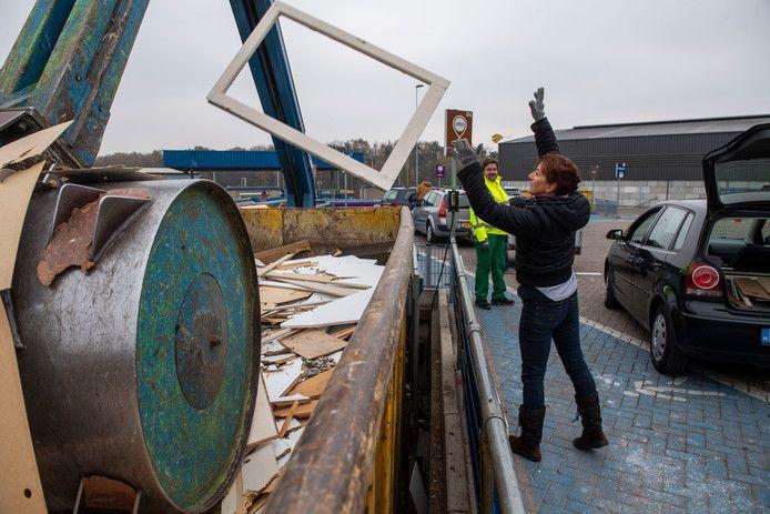 Een vrouw gooit een raamkozijn in een van de vele afvalcontainers van de Tilburgse milieustraat.(archieffoto)