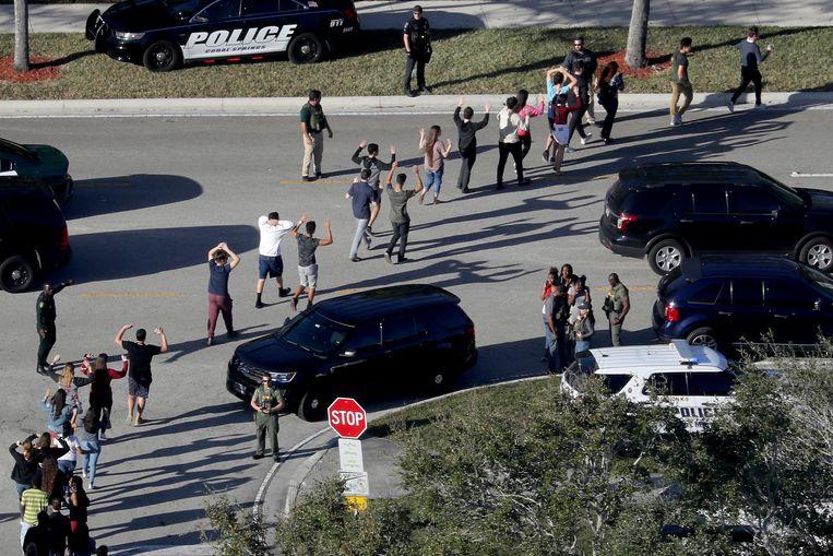 De politie evacueert jongeren van de Stoneman Douglas High School in Parkland op 14 februari vorig jaar.