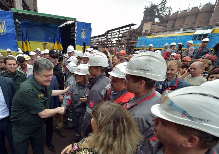 Porosjenko schudt handen van werknemers van een staalfabriek in Marioepol. Beeld afp