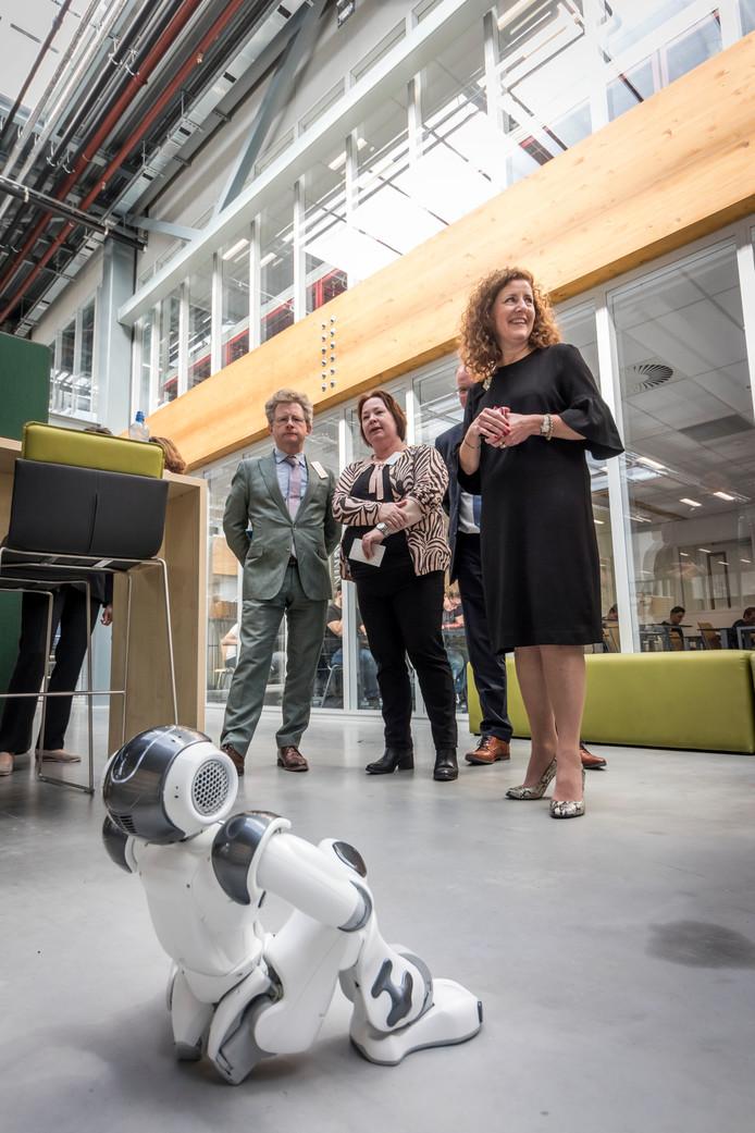 Onderwijsminister Ingrid van Engelshoven bewondert de huisrobot NAO van het Summa College BIC in Eindhoven.