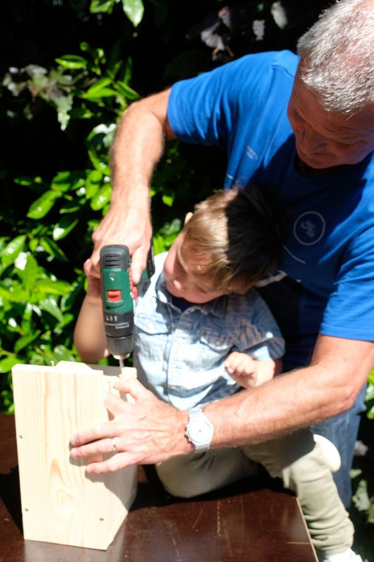 Kinderen en (groot)ouders leren vlinderhuisjes maken in de tuin van de bib.