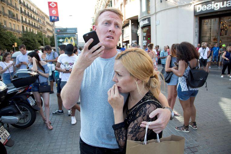Mensen proberen met hun geliefden in contact te komen na de aanslag op de Ramblas. Beeld reuters