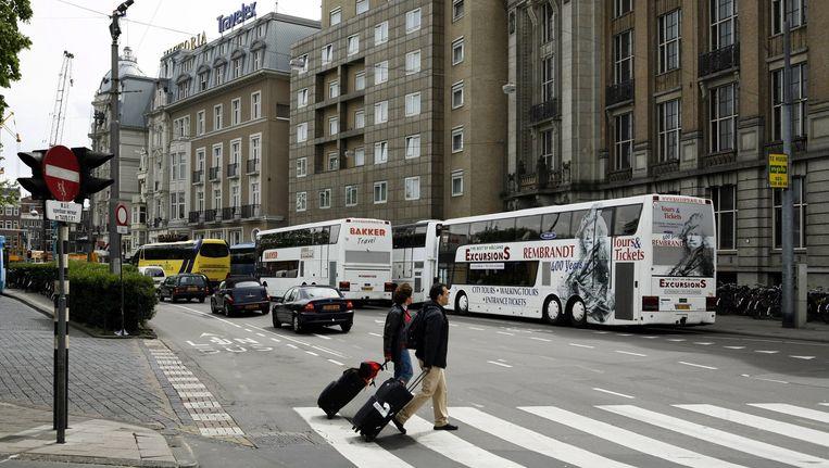 Touringcars zorgen op de Prins Hendrikkade vaak voor overlast, zoals hier bij het Victoria Hotel. Beeld Floris Lok