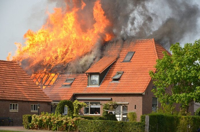 De vlammen slaan uit het dak bij de woningbrand aan de Toverstraat in Baak.