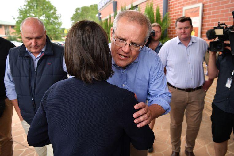 Premier Scott Morrison groet premier Gladys Berejiklian tijdens een bezoek aan een evacuatiecentrum in Picton. Beeld EPA