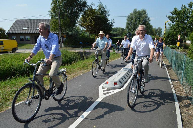 Een delegatie uit beide gemeenten rijdt het nieuwe stuk fietssnelweg in.