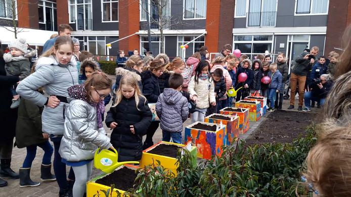Kinderen geven planten water in de beleeftuin.