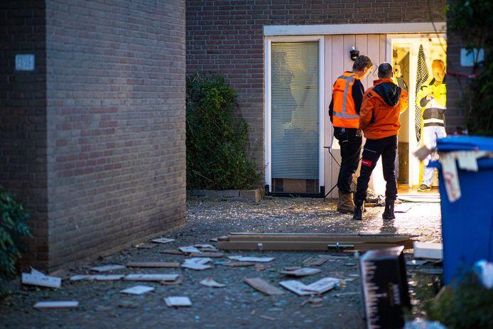 De woning is flink beschadigd door de explosie. Voor het huis liggen delen van de gevel van het huis.