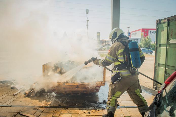De brandweer blust de brand na, nadat omstanders het meeste werk al hebben gedaan.