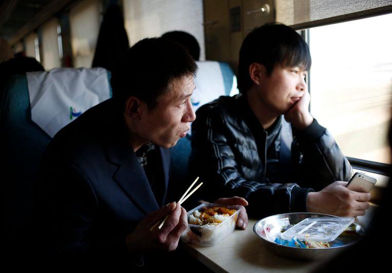 Wang Pengfei (L) in de trein, op weg naar zijn thuisstad Heze. Hij werkt zelf in Peking. Beeld EPA