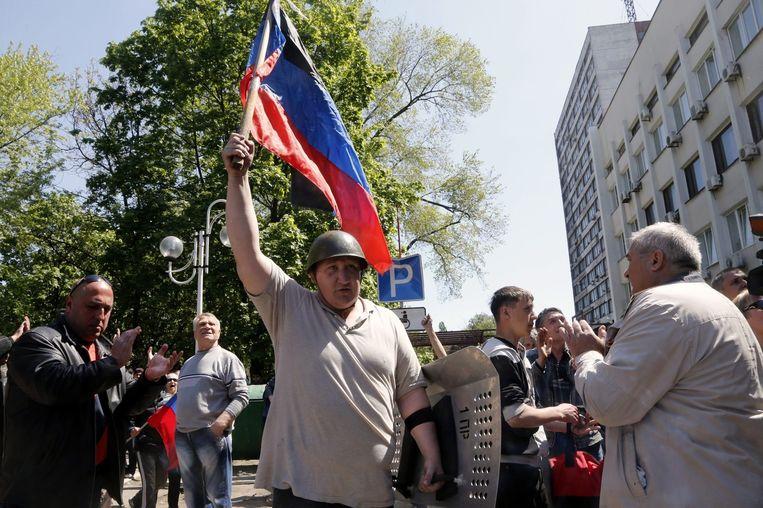 Een man houdt de vlag omhoog van Volkskrepubliek Donetsk die deze week door pro-Russische separatisten is uitgeroepen.