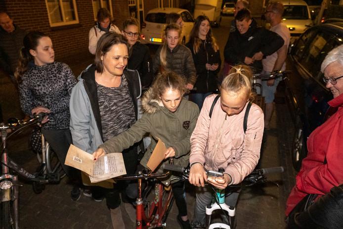 Dominee Marjan Riedijk met Annika van Dijke en Sophie Teunissen die het filmpje van Maria op hun telefoon bekijken