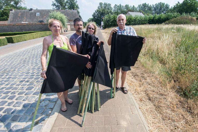 Bewoners Ingrid Van de Berg, Ruud Gelissen, Peggy Jeurissen en Jan Van de Berg bergen hun vlaggen voorlopig op. Rechts de bewuste bouwdgrond.