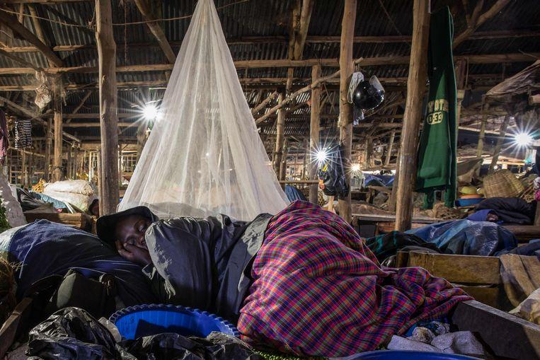 Een handelaar slaapt op de markt naast zijn handelswaar.  Beeld AFP