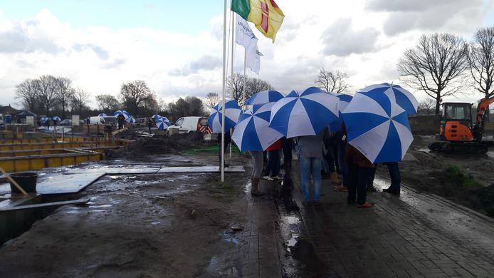 Schuilen bij elkaar voor de regen tijdens de officiele start van de bouw van nieuwbouwwijk de Bulders in Heeze