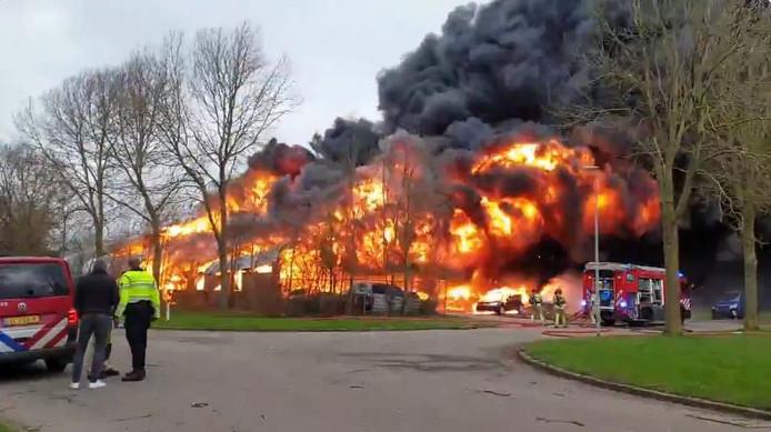 De vlammen slaan metershoog uit het bedrijfspand.