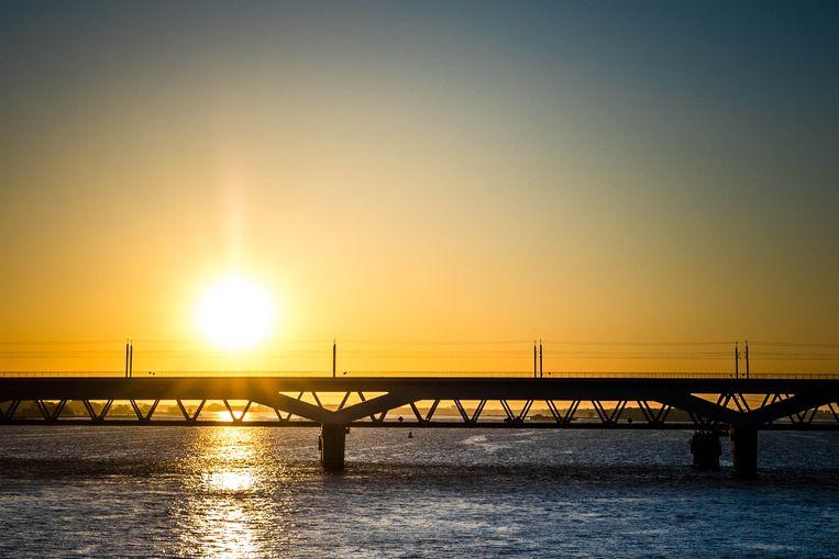 De opkomende zon achter de Moerdijkbrug. Beeld ANP